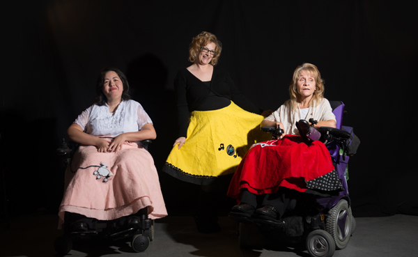 Three woman brightly lit in front of a black background. Each one wearing a skirt. One skirt is pink, the second is yellow and the third is red. Two woman use wheelchairs.