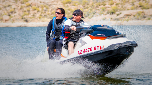 Man. and. woman. in life. vests. zooming. by. on. a. jet. ski.