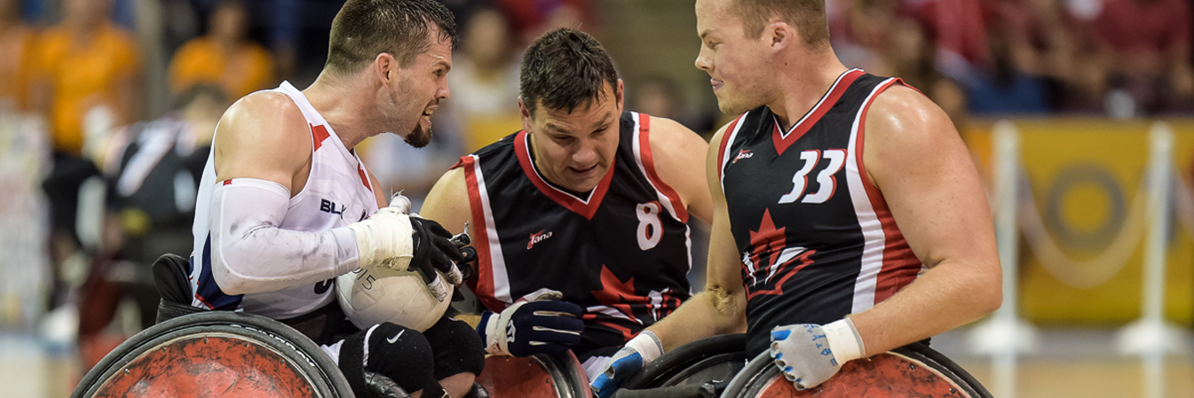 Three men playing wheelchair rugby.