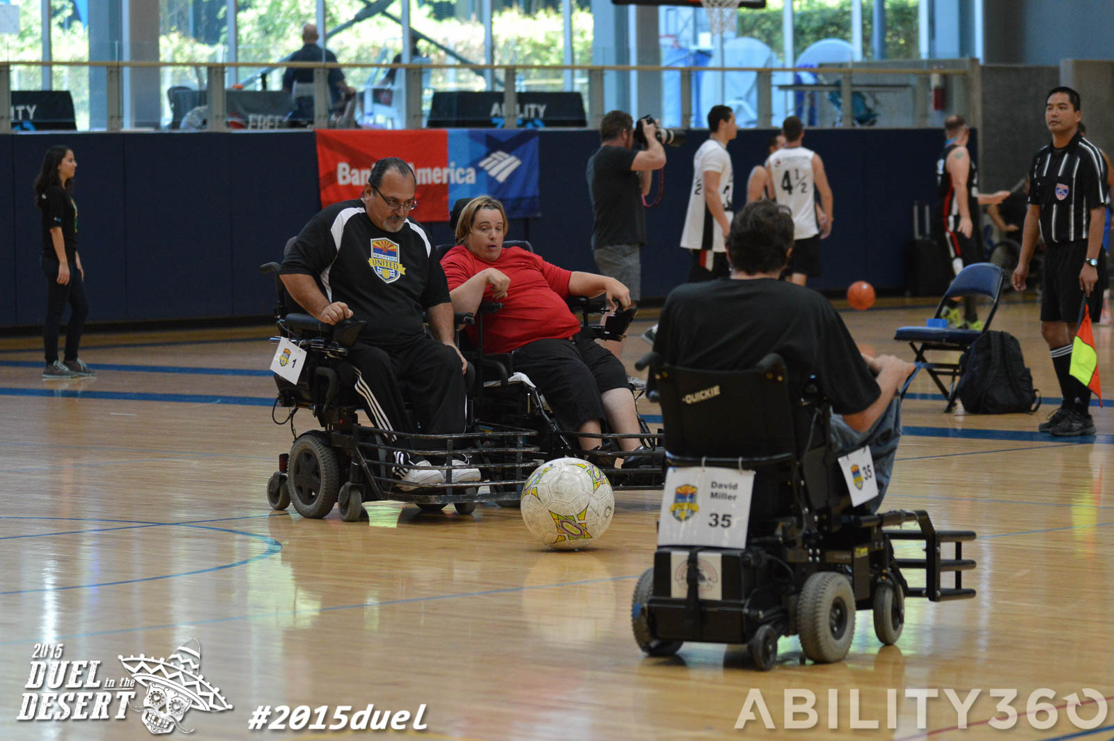 three power chair players. go after the ball. The ball is in the center of the photo