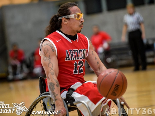 Wheelchair basketball. Arizona player, ball in front of him, facing right, focuses ahead