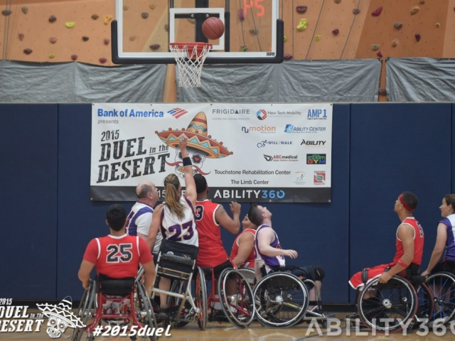 Basketball players look up as ball hovers over the net. Duel poster in background