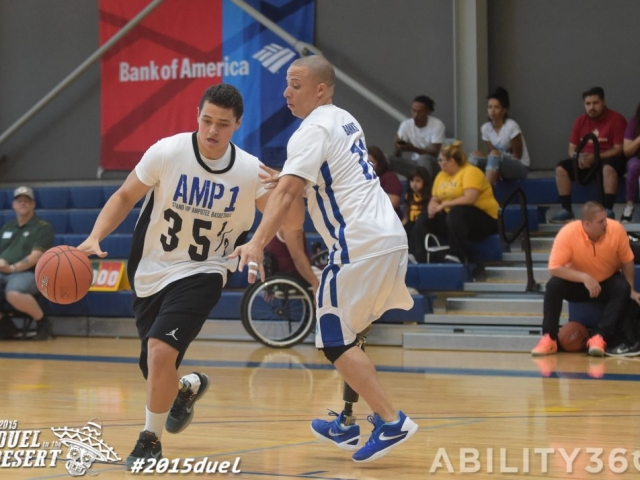 Stand up amputee basketball. Player tries to dribble around opponent