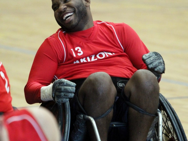 Big guy, big smile. African-American player, number 13 from Arizona leans back. and laughs with someone. off screen