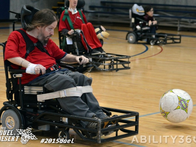 Power Soccer players drive after the large ball