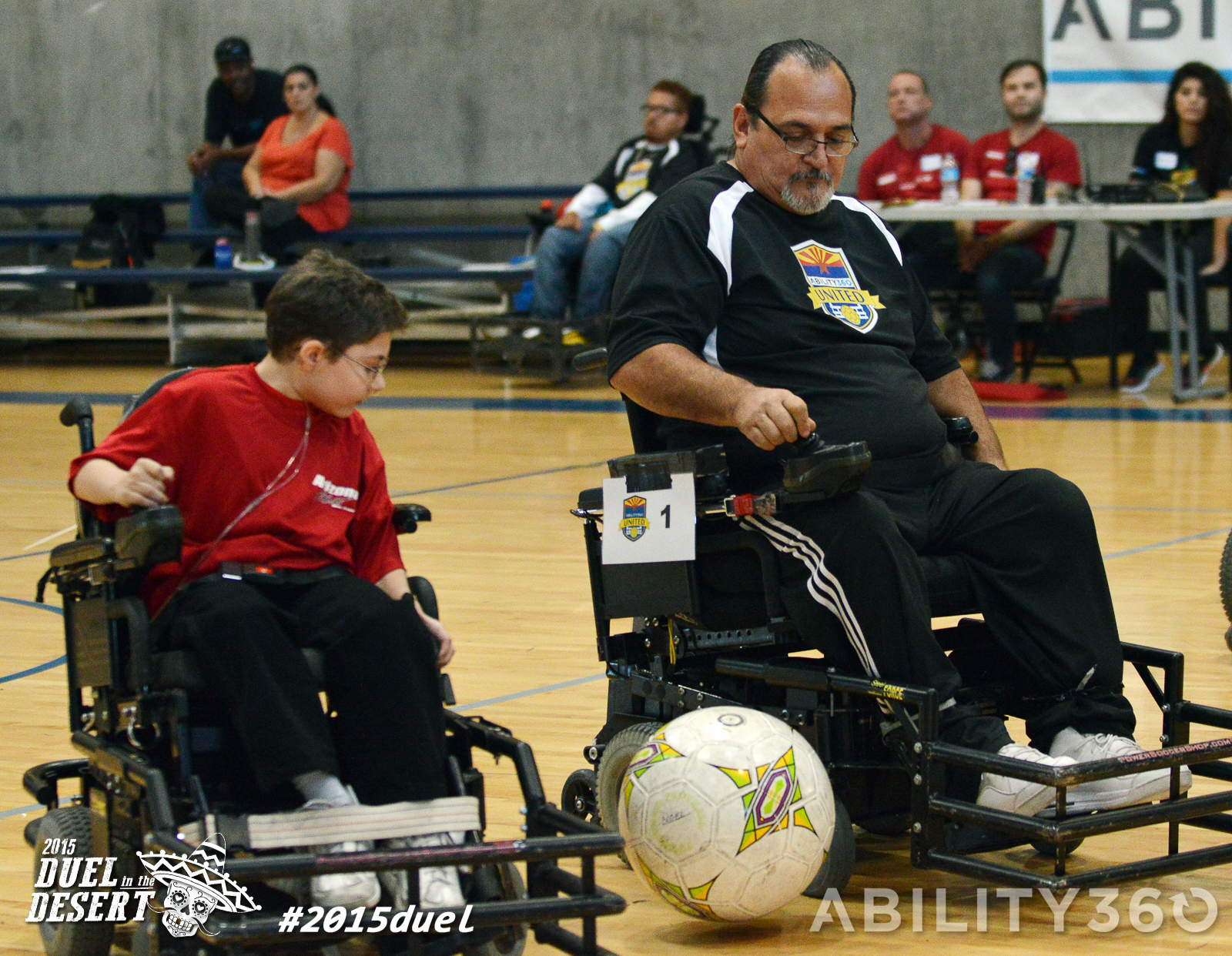 Two power chair players, one child, one adult , different teams, go for the ball between them