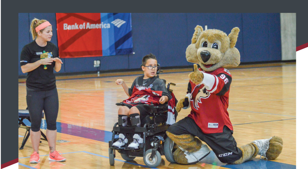 Sara Howser looks on as Phoenix Broyles meets Arizona Coyotes' mascot Howler at Ability360 Fitness Center