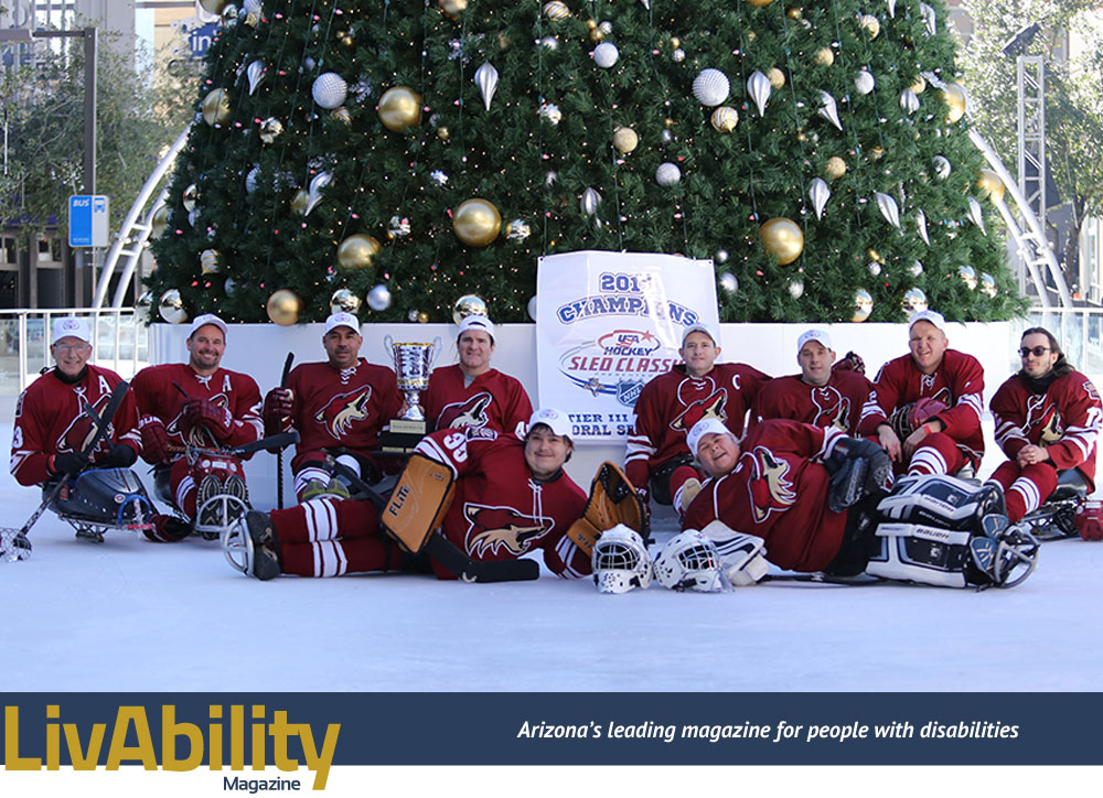 The Phoenix Coyotes sled hockey team pose on the ice.