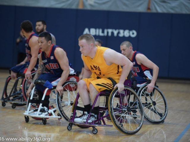 ASU and Wolfpack  basketball playerspush their sport chairs down the court