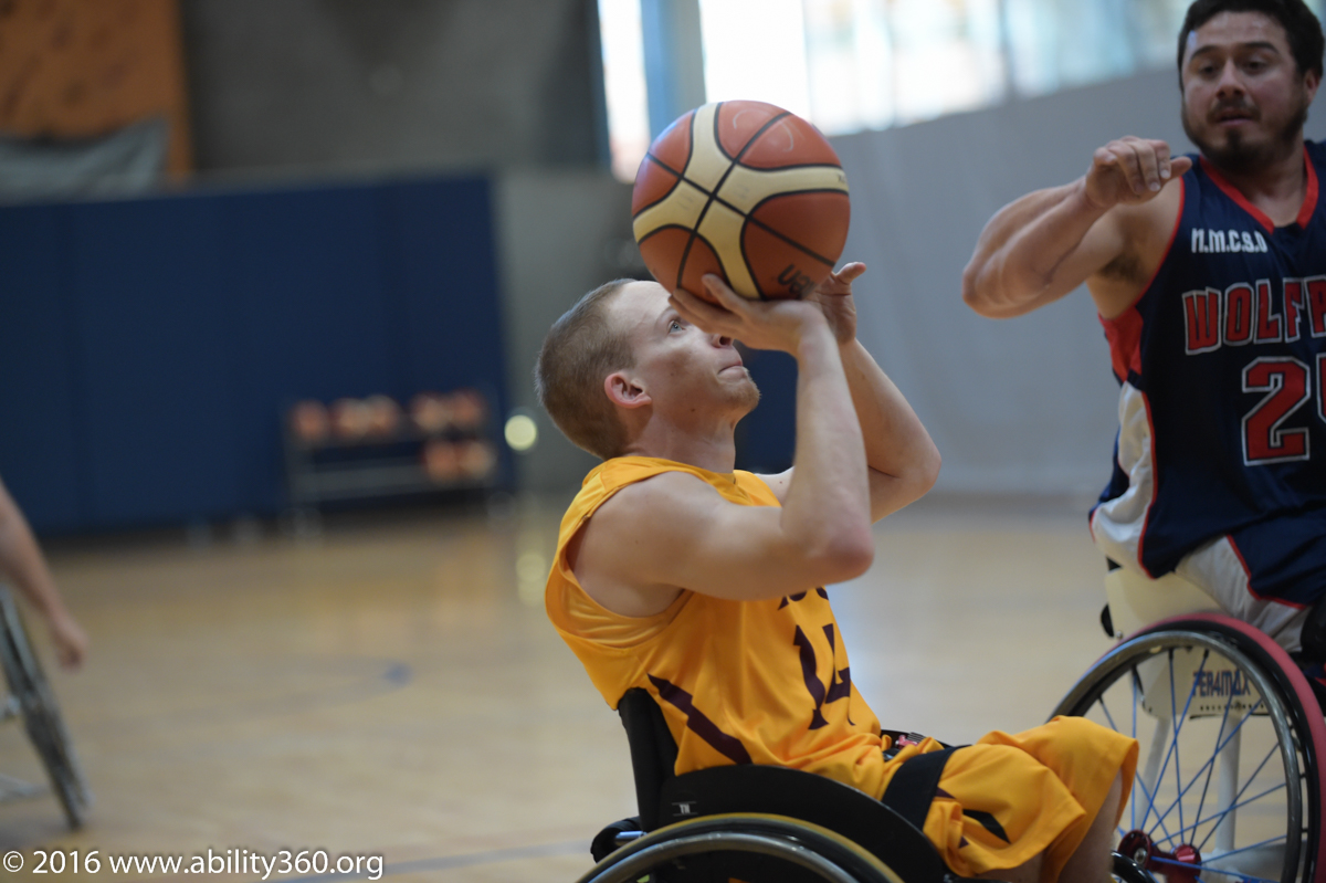 A S U player, ball in the palm of his hand ready to take a shot. opponent hopes to block