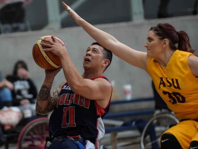 Wolfpack player grimaces and prepares to shoot, while female AS U player, with determined look and arm outstretched, prepares to block