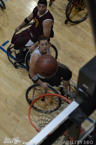 Wheelchair Basketball, view from above the net. as two opponents, watch the ball, from below