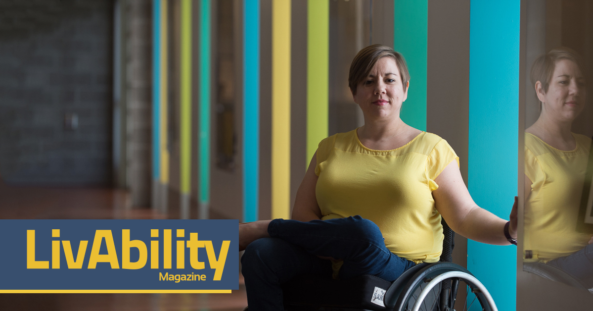 Isabella Mansfield sits in a long hallway. She is wearing a yellow blouse and blue jeans. She smiles at the camera. She is a full-time wheelchair user.