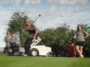 Photograph: A green golf course with desert landscape and cloudy blue sky. Jason Graber hits the golf ball from his Stand Up and Play chair while three other players look on.