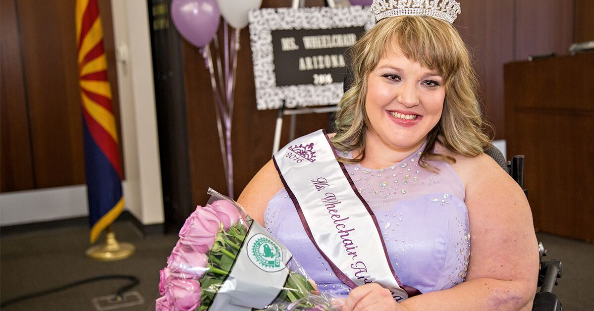 Ms. Wheelchair Arizona Katie Griffith wears a tiara and sash and holds a bouquet