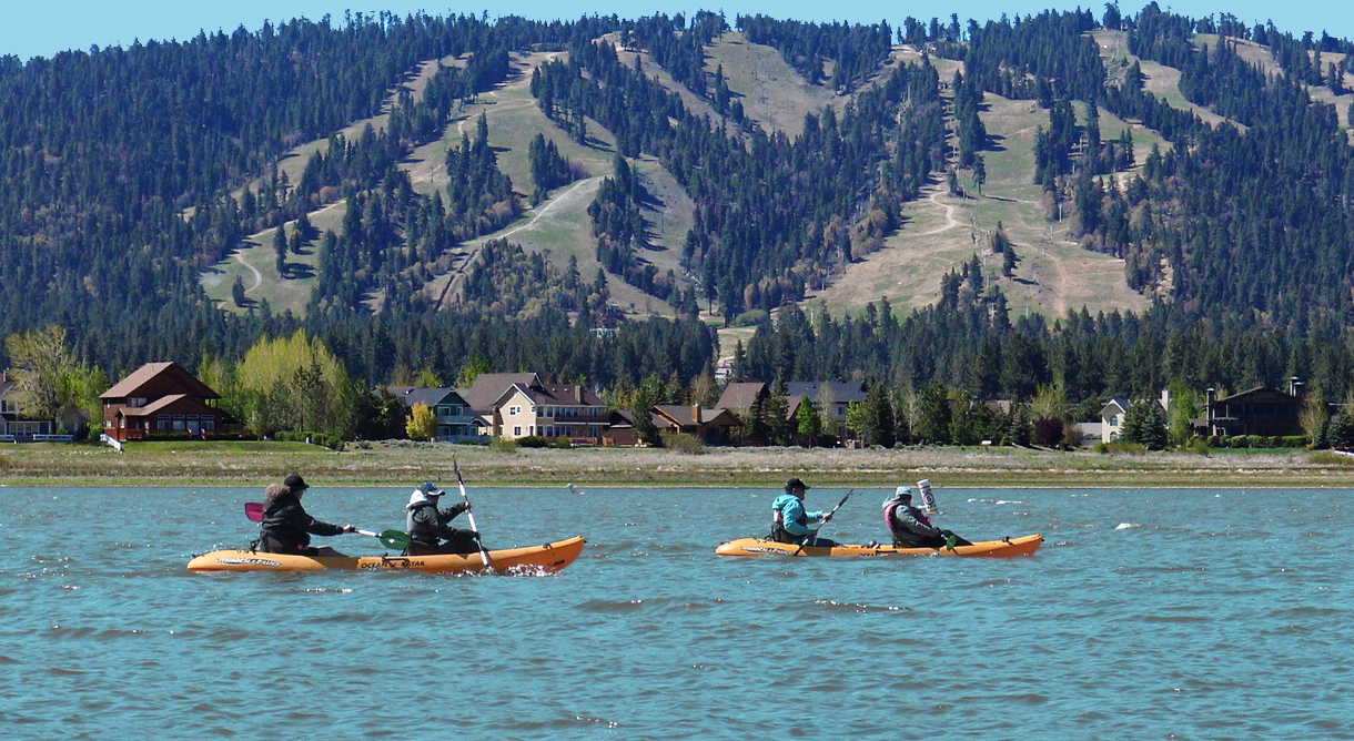2 kayaks on Big Bear Lake. Mountains and lake houses in the background.