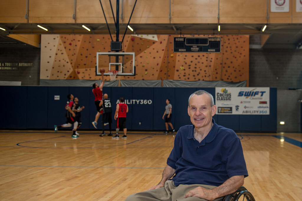 Phil Pangrazio sits in a basketball court while a 6-person game goes on in the background