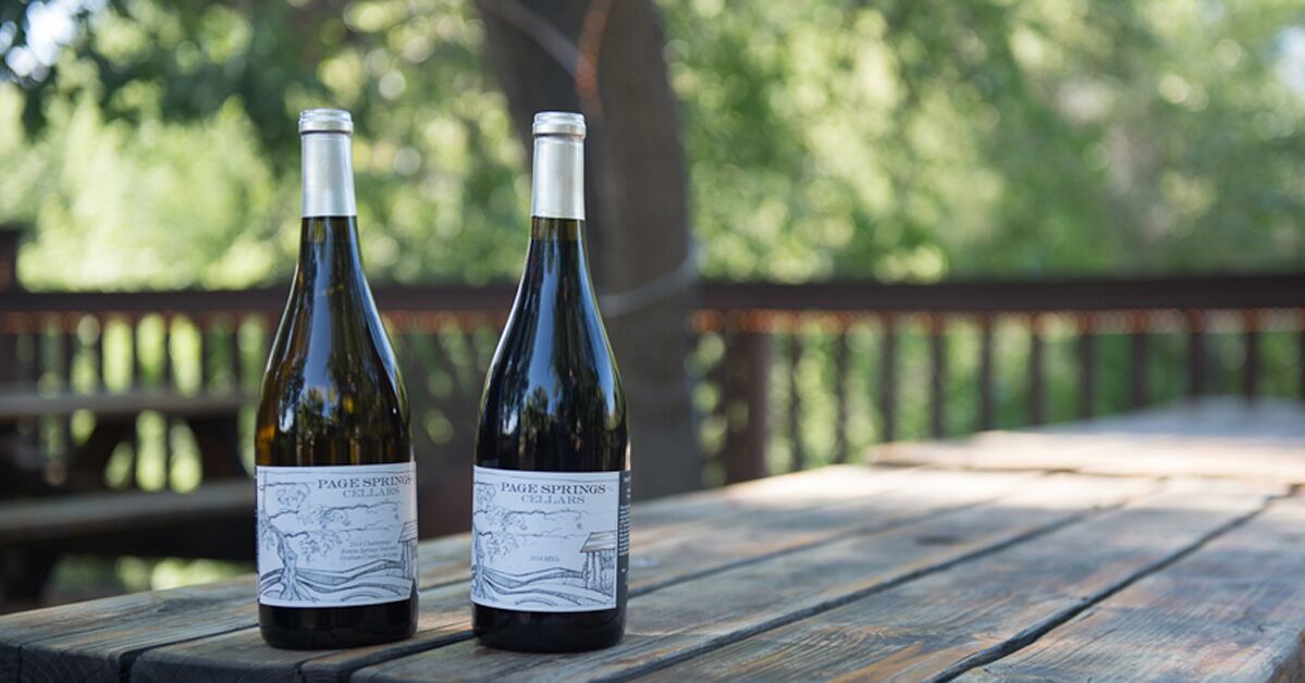 Two wine bottles on a picnic table. There are trees in the background.