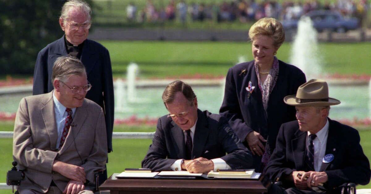 Photo: President George H.W. Bush signs the Americans with Disabilities Act on July 26, 1990. Standing left to right: Rev. Harold Wilkie; and Sandra Parrino, National Council on Disability; Seated left to right: Evan Kemp, Equal Employment Opportunity Commission chairman; and Justin Dart, President's Committee on Employment of People with Disabilities chairman.
