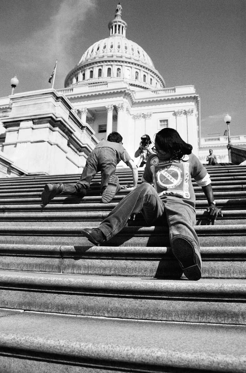 Activists crawl up the steps of the Capitol Building.