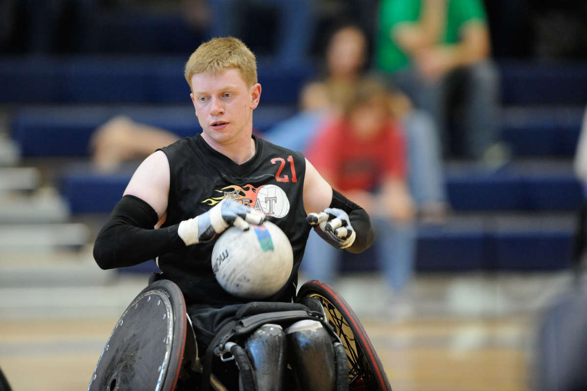 A Wheelchair rugby player holds the ball