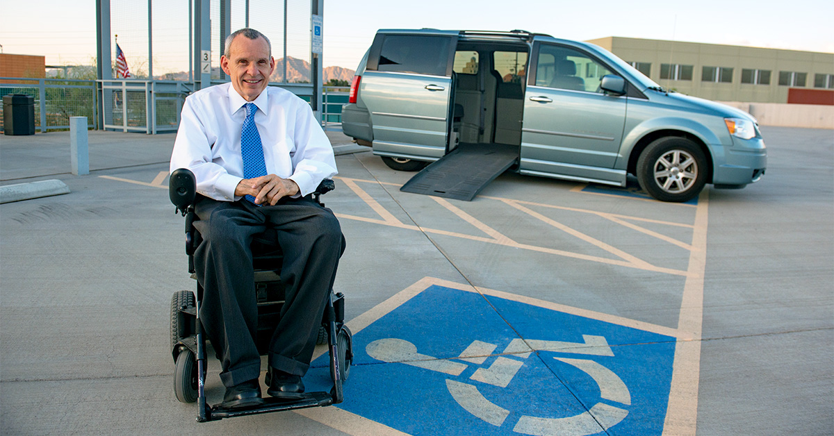 Photo: Phil Pangrazio sits in his wheelchair at the forefront of the photo. He sits on top of the accessible parking symbol. The background features a blue minivan with an open door and lowered ramp atop the Ability 3 60 parking structure. Photo by Loren Worthington