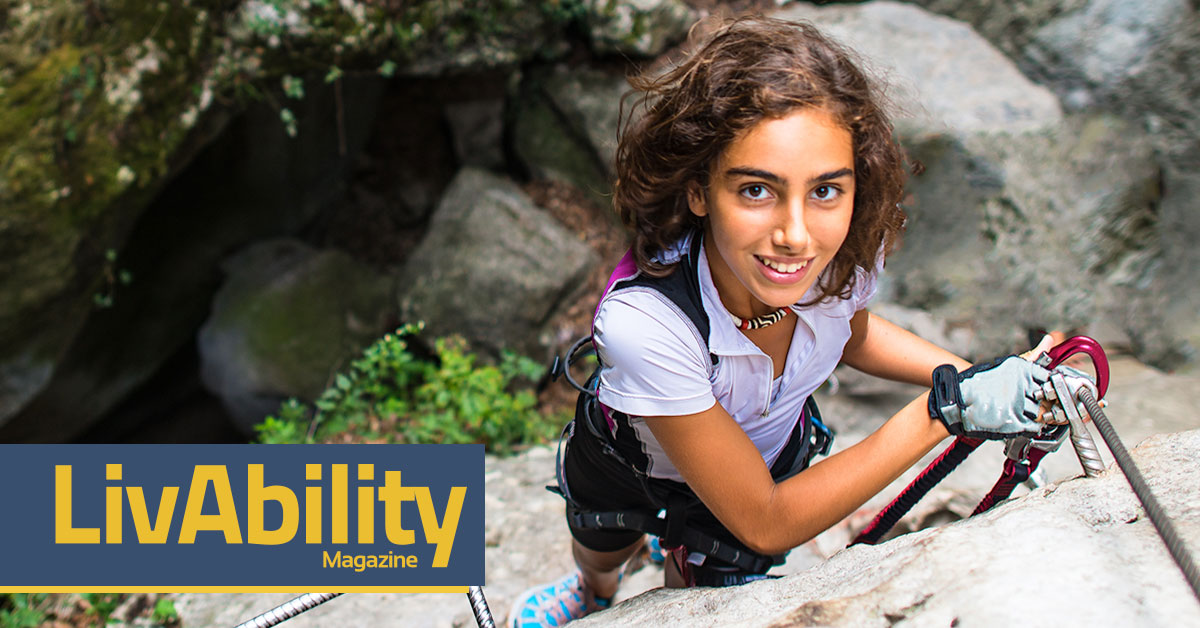 LivAbility Magazine. Young girl with brown hair and a white polo shirt smiles up at the camera as she climbs up the face of a rock wall. The girl is wearing lots of climbing gear, including a climbing belt, gloves and chalk. The background shows a crevice in between the cliffs. The other cliff face is green and mossy. The Breaking Barrier logo is overlaid on the photo in lower left corner.