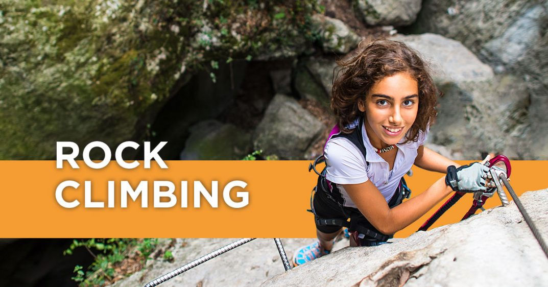 Rock Climbing. Young girl with brown hair and a white polo shirt smiles up at the camera as she climbs up the face of a rock wall. The girl is wearing lots of climbing gear, including a climbing belt, gloves and chalk. The background shows a crevice in between the cliffs. The other cliff face is green and mossy. The Breaking Barrier logo is overlaid on the photo in lower left corner.