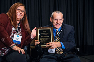 Photo: Phil Pangrazio, President and CEO of Ability 3 60 smiles as he holds up the NCIL President's Award for the camera. Phil is dressed in a sports jacket, blue shirt and gold and blue striped tie.