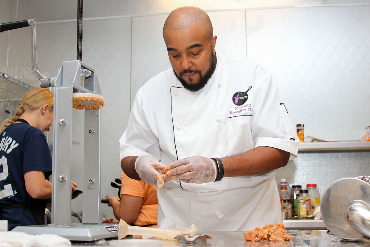 A black man in a chef's jacket and plastic gloves on his hands prepares food to be grilled.