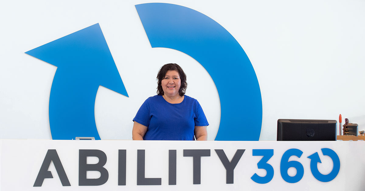Maribel Sanchez, a woman in a blue shirt stands behind a desk and in front of the Ability360 logo.