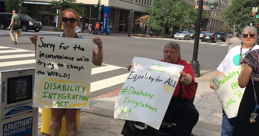 Women and men with various disabilities hold up signs to advocate for disability rights. Their signs ask for support of the Disability Integration Act.