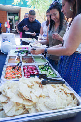 A buffet of taco ingredients attracts a line of people in the Ability 360 Courtyard.