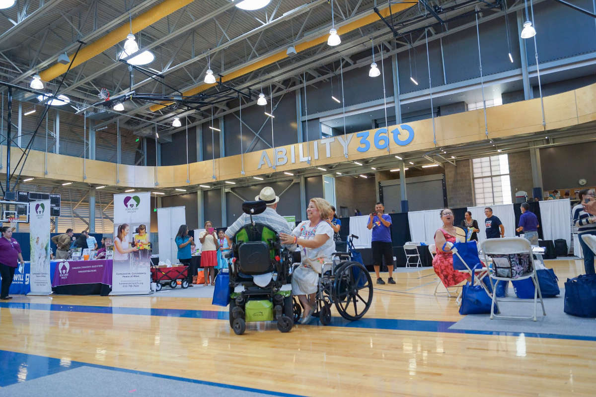 A man and a woman in wheelchairs greet each other in Ability360's basketball court, which is filled with information booths.