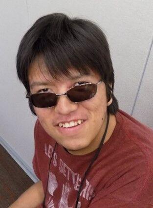 Mateo TreeTop smiles at the camera in a brick red shirt