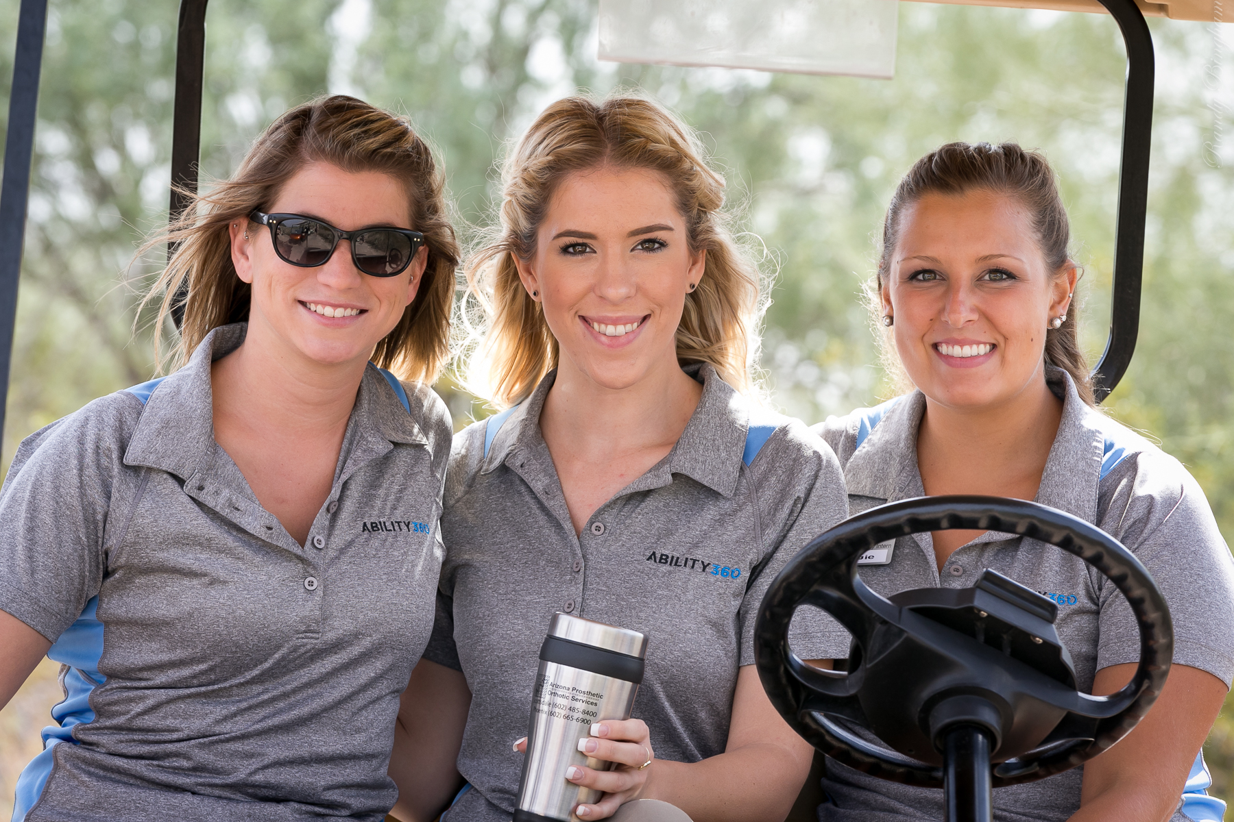 3 female Ability360 staff smiling while driving a golf cart.