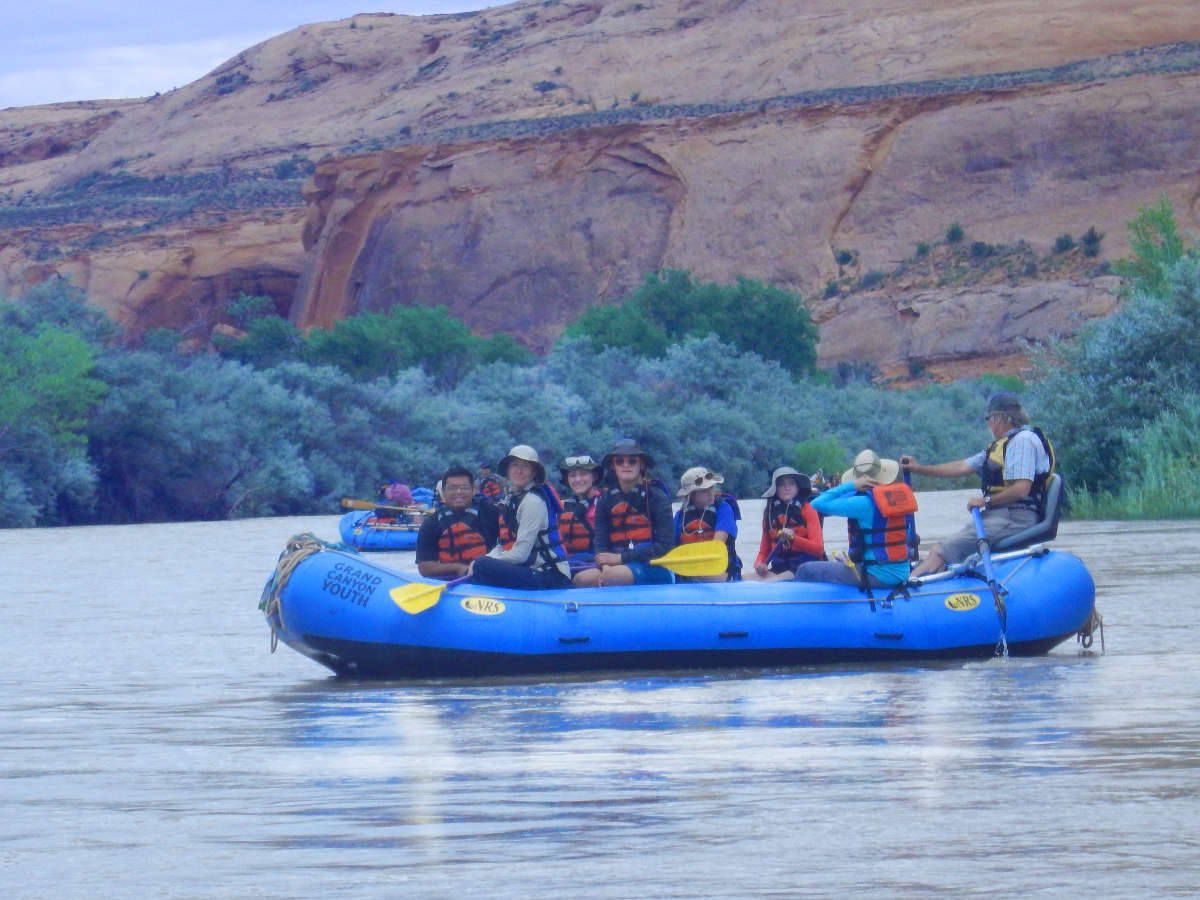 Campers wearing life jackets smile from a whitewater raft.