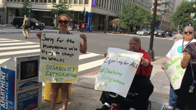 People hold signs supporting the Disability Integration Act.