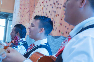 Three young Hispanic men play instruments and sing in front of the Ability 3 60 rock wall.