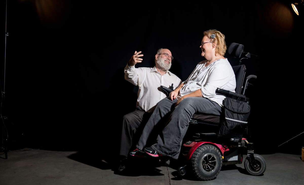 A seated man gestures to a woman in a power chair onstage