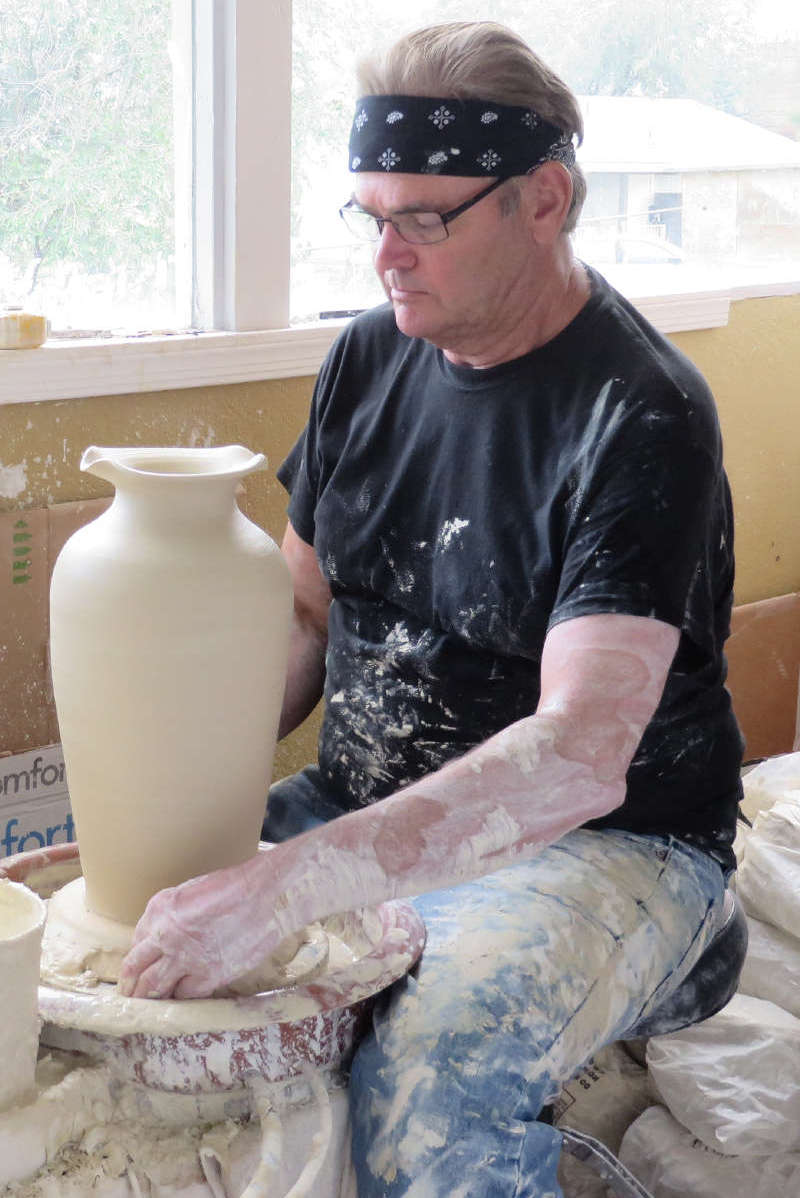 JD sculpts a clay vase at a pottery wheel.