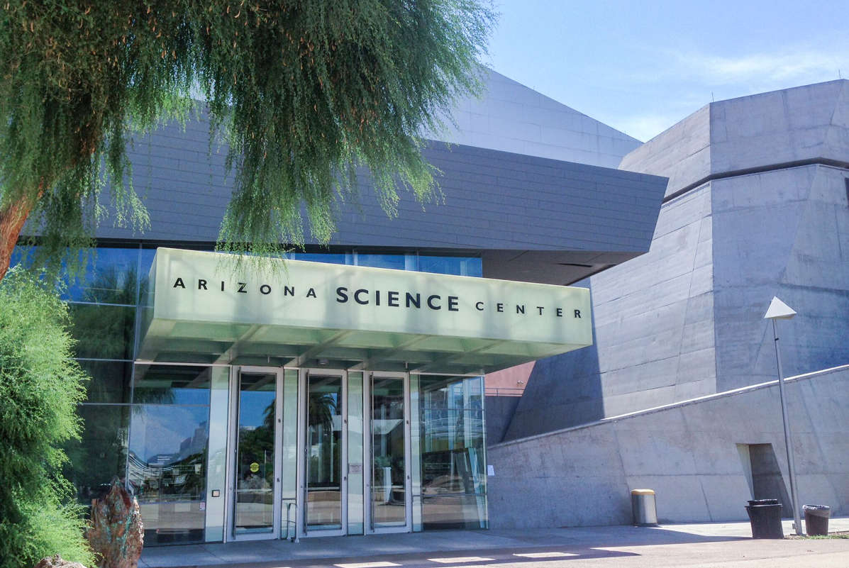 The entrance to the Arizona Science Center, a gray stone building with glass doors