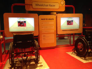 Two floor-mounted manual wheelchairs set up for a stationary racing game with screens in front of each chair.