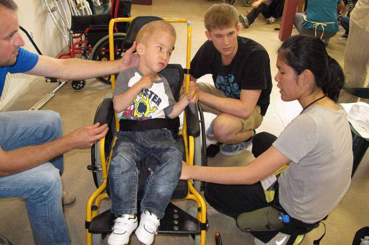 Three adults pose next to a young boy in a used wheelchair.