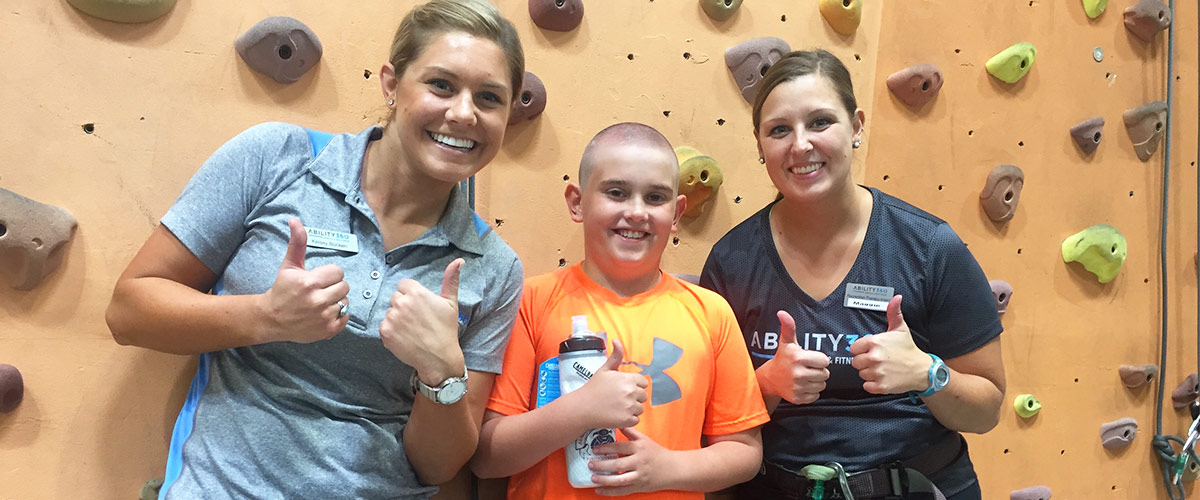 Two instructor of the Breaking Barriers program pose in front of rock wall with a young boy participant, all three have thumbs up.
