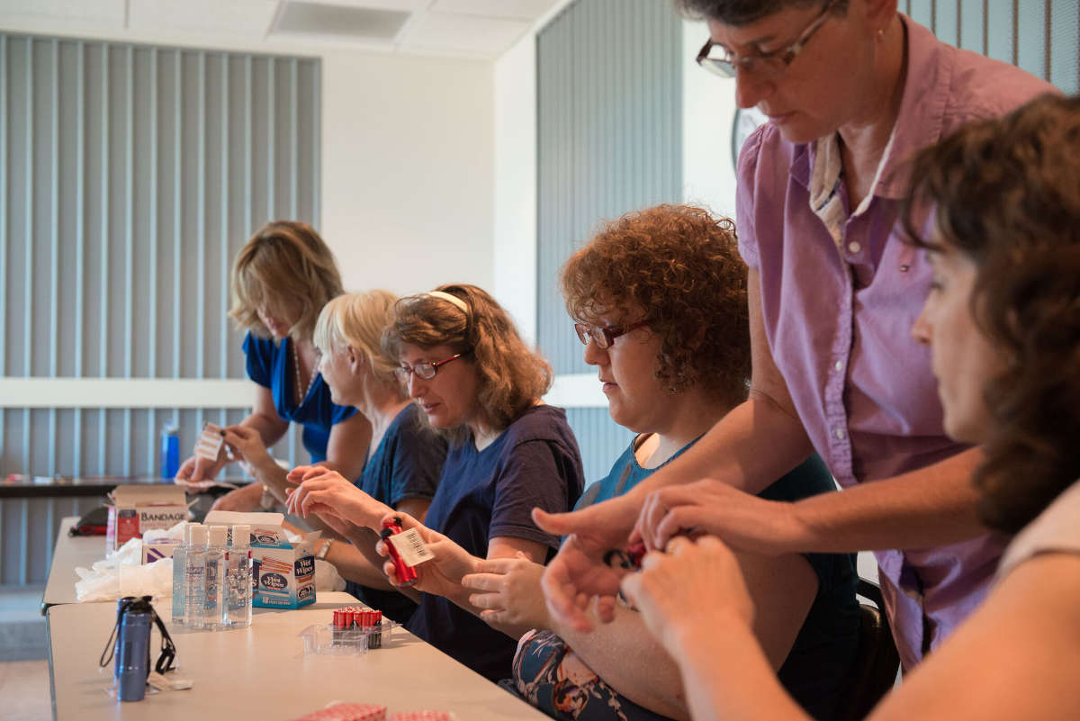 Members of the Independent Living Council assemble first aid kits at a table.