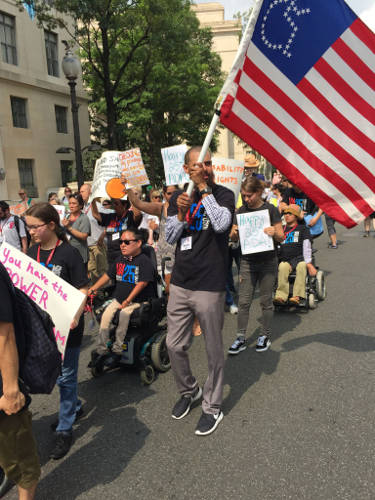 People with disabilities march down Pennsylvania Avenue. One marcher holds an American flag with the stars in the shape of a handicapped sign