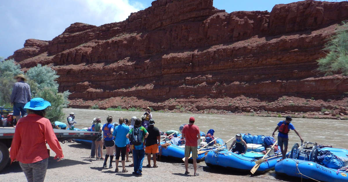 PHOTO: Red rock mountains rise in the background against a bright blue sky. In the middle ground is a river. In the foreground are 6 blue inflatable river rafts being loaded with camping gear by a group of people of mixed ages, gender and ethnicity. One raft holds an empty wheelchair.