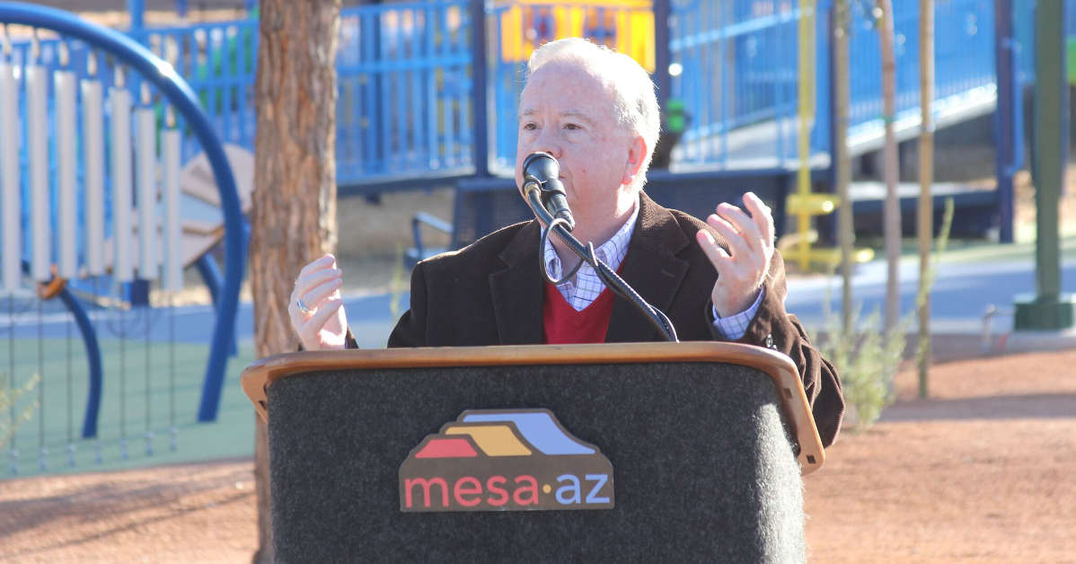 PHOTO: an older man stands at a podium. The LOGO reads Mesa Arizona. There is a playground in the background.
