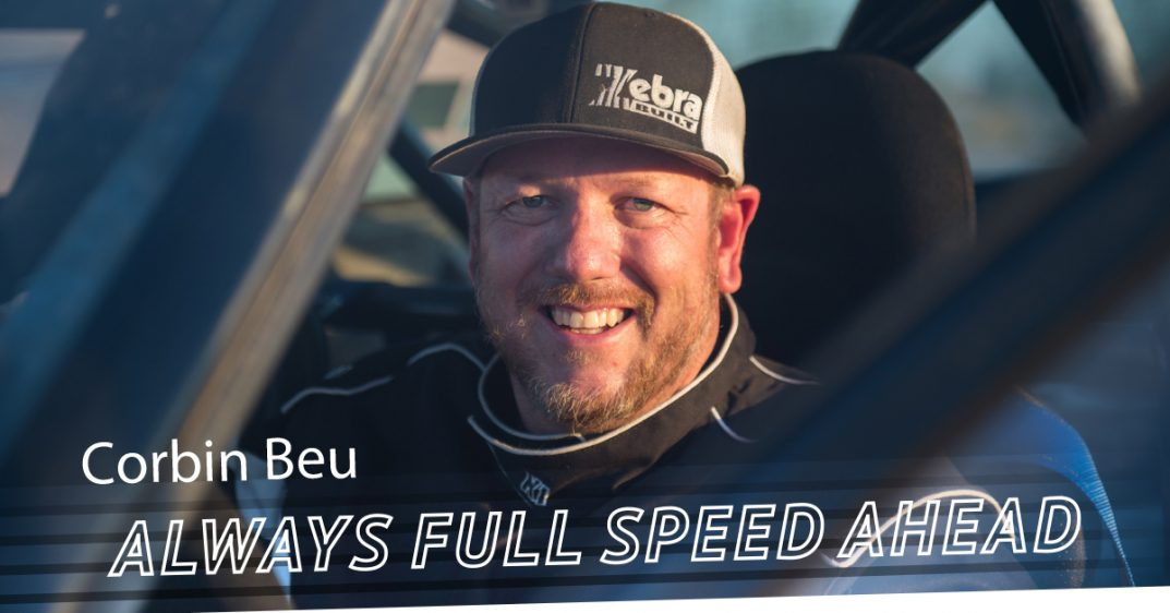 "PHOTO: Adaptive racer Corbin Beu sits in his car and smiles at the camera. The words ""full speed ahead"" are displayed below his face."